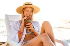 Image of beautiful young woman 20s in straw hat drinking exotic. Cocktail while sunbathing in deck chair at sea coast during summer sunrise stock image