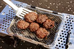 Burgers Being flipped on a Portable BBQ Royalty Free Stock Photos
