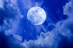Full Moon in The Night Sky. Image of big bright full moon glowing in the blue sky with clouds at night during a light rain stock image