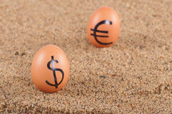 Image of big white eggs with dollarand euro  signs on a sand. Royalty Free Stock Photo