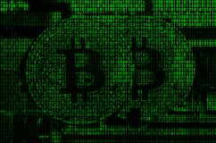 Image of the binary code from bright green digits, through which the image of the physical bitcoin royalty free stock photo