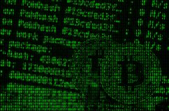 Image of the binary code from bright green digits, through which the image of the physical bitcoin stock image