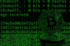 Image of the binary code from bright green digits, through which the image of the physical bitcoin royalty free stock image