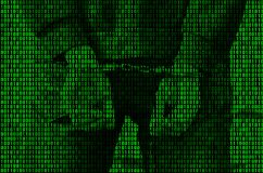 An image of a binary code from bright green figures, through which the image of an arrested and handcuffed person royalty free stock photos