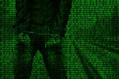 An image of a binary code from bright green figures, through which the image of an arrested and handcuffed person stock photography