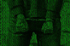 An image of a binary code from bright green figures, through which the image of an arrested and handcuffed person royalty free stock images