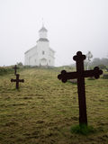 Image of black iron crosses standing at the cemetery on the background of the Norwegian Church Stock Image