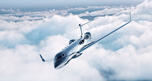 Image of black luxury generic design private jet flying in blue sky. Huge white clouds at background. Business travel Royalty Free Stock Image