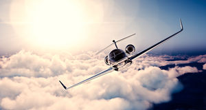 Image of black luxury generic design private jet flying in blue sky at sunset. Huge white clouds background. Business Stock Photography