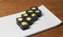 Image of black sushi with avokado on plate in restaurant. Close image of black sushi on table Stock Photo