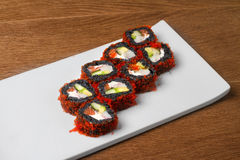 Image of black sushi with salmon on plate in restaurant. Close image of black sushi on table Stock Photos