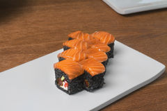Image of black sushi with salmon on plate in restaurant. Close image of black sushi on table Stock Images