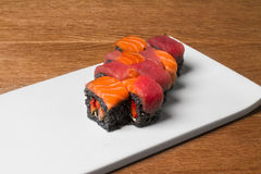 Image of black sushi with salmon on plate in restaurant. Close image of black sushi on table Royalty Free Stock Image