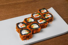 Image of black sushi with salmon on plate in restaurant. Close image of black sushi on table Royalty Free Stock Images