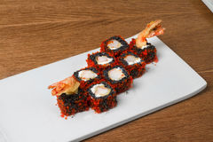 Image of black sushi with shrimp on plate in restaurant. Close image of black sushi on table Royalty Free Stock Images