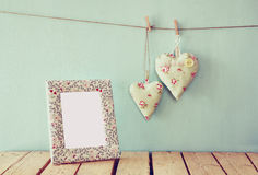 Image of blank frame and hanging fabric hearts on rope in front of wooden background. retro filtered image Royalty Free Stock Photos
