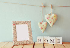 Image of blank frame next to wooden blocks with word home, and hanging fabric hearts on rope in front of wooden background Stock Photos