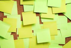 Image of blank green and yellow sticky notes. On cork bulletin board Stock Image