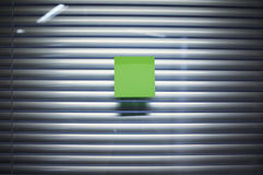 Image of blank sticky note on office glass wall with jalousie Stock Images