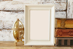 Image of blank wooden frame, next to old books. template Royalty Free Stock Images