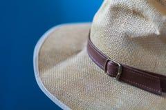 Image bleue brouillée d'un chapeau crème avec la frange blanche et la courroie brune image libre de droits