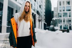 Image of blonde girl in hood and in jacket against winter day. Building background stock images
