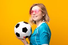 Image of blonde in pink glasses with soccer ball on orange background royalty free stock images