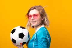 Image of blonde in pink glasses with soccer ball on orange background royalty free stock photos