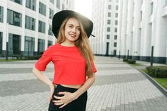 Image of blonde in red jacket and black hat. In city against background of modern buildings on summer day Stock Photos