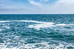 Blue sea with waves and sky with clouds Royalty Free Stock Image