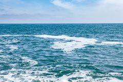 Blue sea with waves and sky with clouds Royalty Free Stock Photo