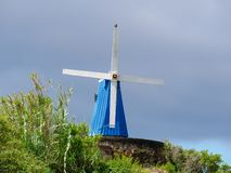 Image of blue wooden wind mill on a stone base royalty free stock photos