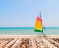 Image of blurred sea blue-sky and colorful boat with coconut wooden plank Royalty Free Stock Image