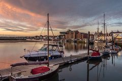 Sunrise at Wells Quay. Image of boats moored on a pontoon at Wells next the Sea harbour. The harbour buildings and quay in the background. Sunrise is fast royalty free stock images