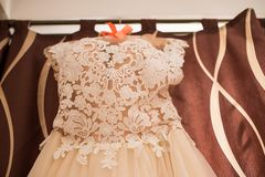Image of the bodice of a beige wedding dress on a hanger. Dress Royalty Free Stock Photo