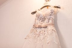 Image of the bodice of a beige wedding dress on a hanger. Wedding Royalty Free Stock Photo