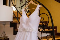 Image of the bodice of a white wedding dress on a wooden hanger Stock Photography