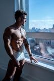 Image of bodybuilder posing standing at window Royalty Free Stock Photos