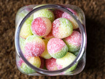Image of boiled candy inside a glass jar. Close up photo of round boiled sweets in a jar. They are rhubarb and apple green and red in color. There are sugar stock image