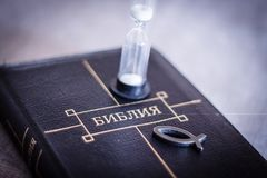 Image of book Bible close-up in leather black binding with zipper with christian fish icon and hourglass on gray blurry background. With black vignette Stock Image