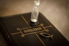 Image of book Bible close-up in leather black binding with zipper with christian fish icon and hourglass on gray blurry background. With black vignette Royalty Free Stock Photography