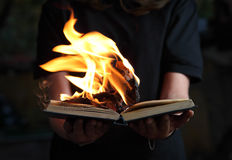 Image of book burning in woman hands in dark forest Stock Image