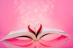 Image of book pages into a heart shape of pink background Stock Image