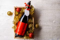 Image of bottle of wine in box with tinsel, Christmas balls Stock Photos