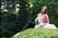 Image from bottom of brunette sitting with dog on green lawn Royalty Free Stock Image