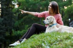 Image from bottom of girl pointing forward next to dog on green lawn royalty free stock photos