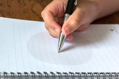 Child's Hand Holding Ballpoint Writing on Notepad royalty free stock photo