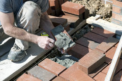 Brick mason applying mortar. Stock Images