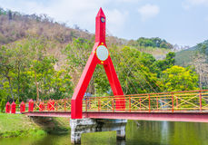 image of Bridge painted in red leading to a green forest Stock Photos