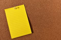 Sticky Note and Corkboard. An image of a bright sticky note pinned to a wooden cork-board stock image
